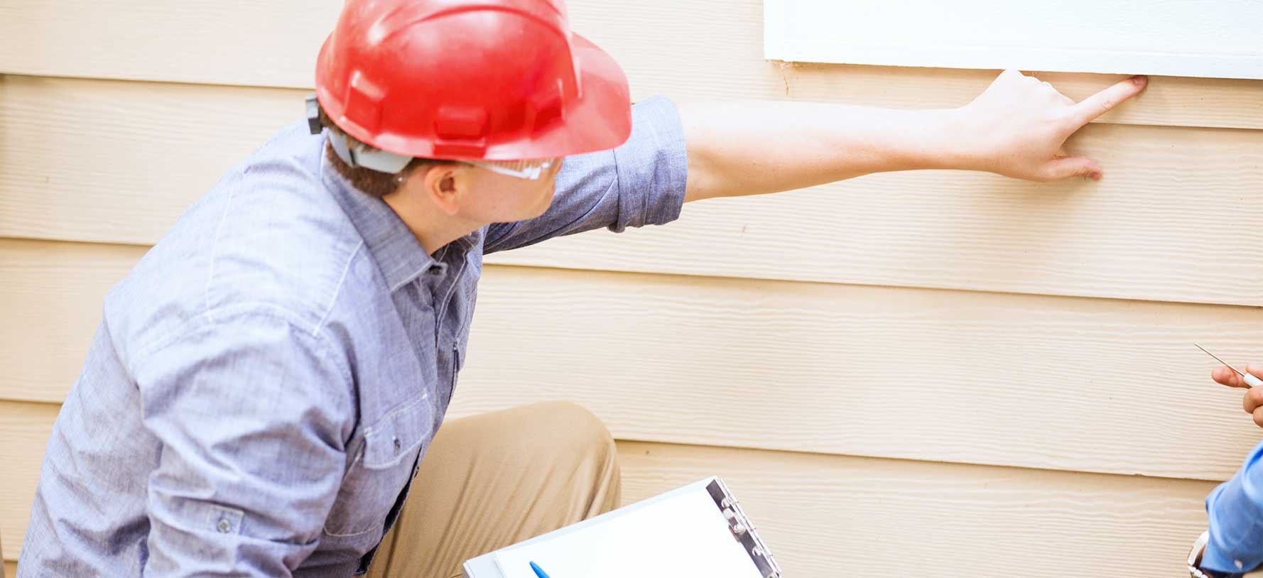 A home inspector reviews the side of a home